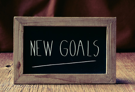 coherence: a wooden-framed chalkboard with the text new goals written in it, placed on a rustic wooden surface
