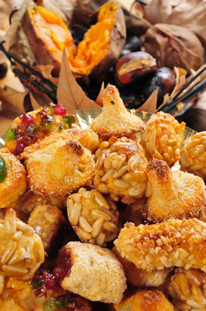 closeup of a plate with Catalan panellets, and some roasted chestnuts and sweet potatoes in the background, as a typical snack in All Saints Day in Catalonia, Spain