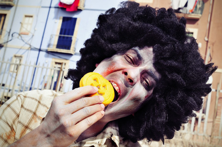 afro hairdo: closeup of a scary zombie with an afro hairdo eating a pumpkin-shaped cookie