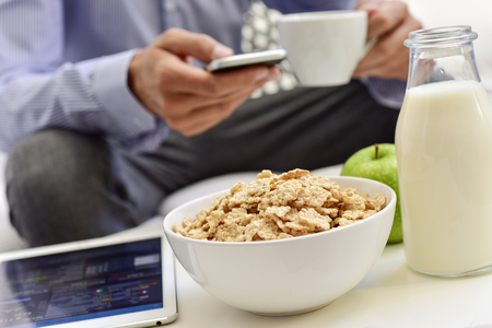 a young caucasian businessman checking his smartphone and his tablet sitting next to a table set for breakfast, with a cup of coffee, an apple and a bowl with cereals