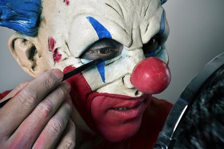 psychopath: closeup of a young man making up himself as an evil clown, using a mirror