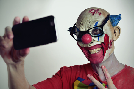 psycho social: portrait of a scary evil clown taking a selfie with his smartphone, while giving a V sign Stock Photo