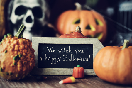 carved pumpkin: a chalkboard with the text We witch you a happy Halloween, surrounded by some different pumpkins, placed on a rustic wooden surface, and some scary ornaments, such as a skull or a carved pumpkin