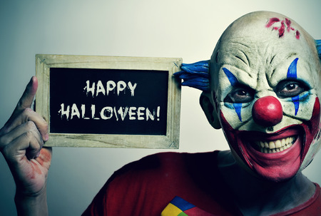 Evil clown: portrait of a scary evil clown with a chalkboard with the text happy Halloween written in it