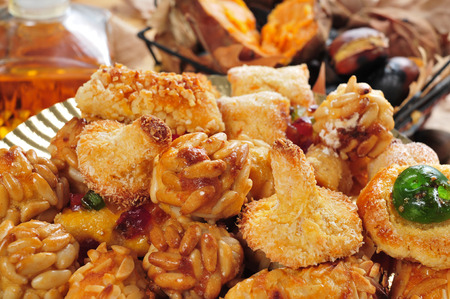 tots: closeup of a plate with Catalan panellets, some roasted chestnuts and sweet potatoes in a basket, and sweet wine in a glass bottle, typical snack in All Saints Day in Catalonia, Spain