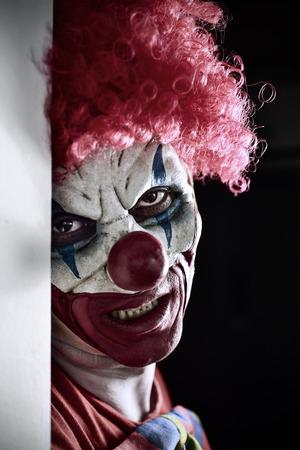 portret van een enge kwade clown tegen een donkere achtergrond Stockfoto