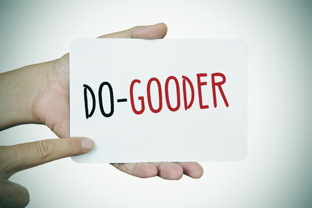 helpfulness: closeup of the hands of a young man showing a signboard with the text do-gooder written in it