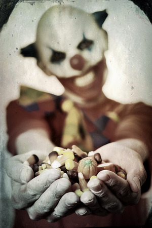 a scary evil clown with a pile of different Halloween candies in his hands, offering them to the observer, with a dramatic effect