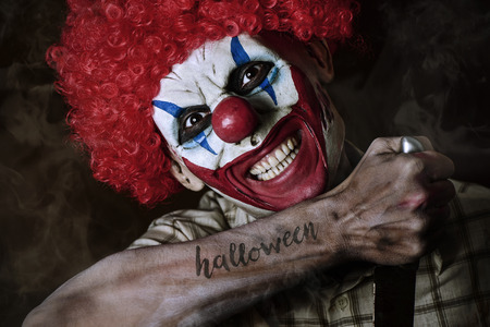a scary evil clown with a big knife in his hand and the word Halloween simulating a tattoo in his forearm, against a dark background