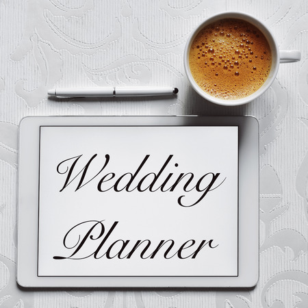 event planner: high-angle shot of cup of coffee, a digital pen and a tablet computer with the text wedding planner in its screen placed on a flower-patterned white surface