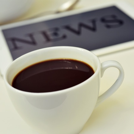 abreast: closeup of a cup of coffee and a tablet computer with the word news in its screen Stock Photo