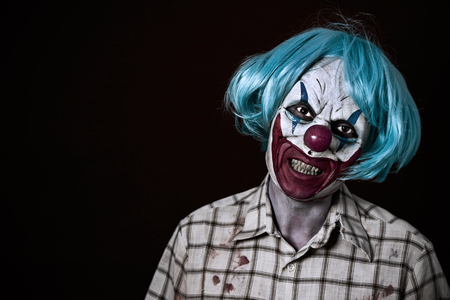 Evil clown: portrait of a scary evil clown wearing a ragged and dirty shirt with blood stains and a blue wig, against a dark background Stock Photo