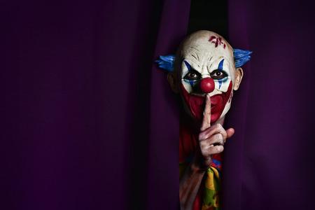 een enge kwade clown turend van een paarse podium gordijn, met zijn wijsvinger in de voorkant van zijn lippen, vragen om stilte, met een negatieve ruimte aan de ene kant