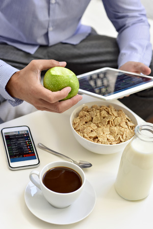 workaholic: a young caucasian businessman checking his tablet and his smartphone sitting next to a table set for breakfast, with a cup of coffee, an apple and a bowl with cereals