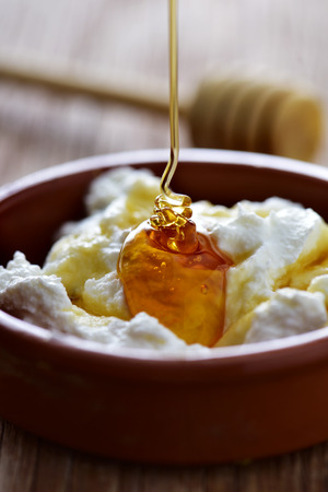 mel: closeup of a earthenware bowl with mel i mato, a typical dessert in Catalonia, Spain, made with whey cheese and honey, on a rustic wooden table