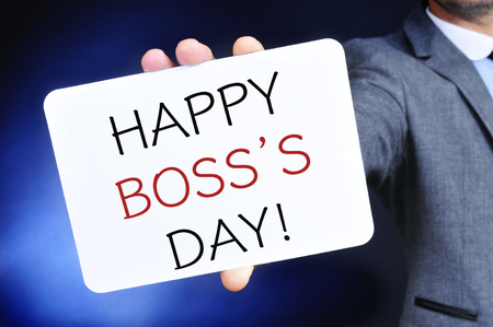 headman: a young caucasian businessman shows a signboard with the text happy boss day written in it