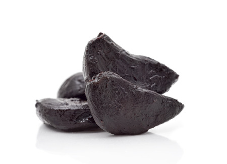 closeup of some black garlics on a white background