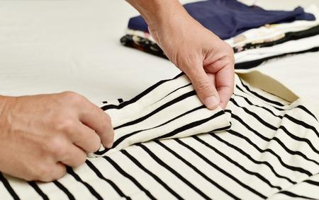 soltería: primer plano de un hombre caucásico joven plegable una camisa de polo, con una pila de ropa doblada en el fondo