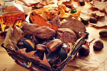 closeup of some roasted chestnuts and sweet potatoes in a basket, and a plate with Catalan panellets, and a glass bottle with sweet wine, typical snack in All Saints Day in Catalonia, Spain Standard-Bild