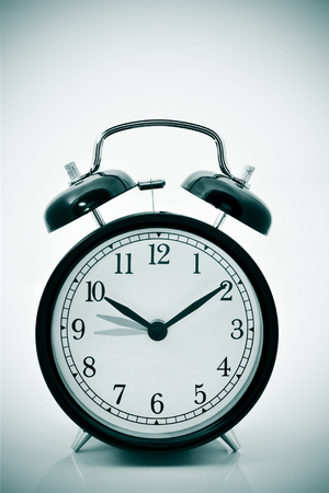backward: closeup of an alarm clock adjusting backward one hour at the end of the summer, with a vignette added Stock Photo