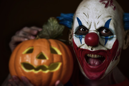 closeup of a scary evil clown holding a carved pumpkin next to his head Stock Photo