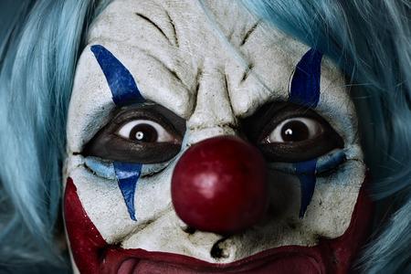 Close-up van een eng kwade clown die een blauwe haar pruik draagt Stockfoto