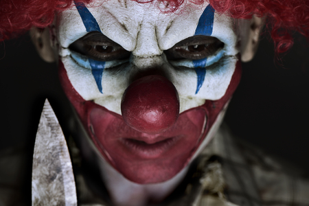 Evil clown: closeup of a scary evil clown wearing a ragged shirt, holding a big knife next to his face