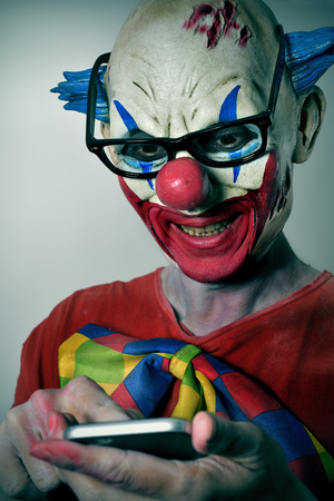 psycho social: portrait of a scary evil clown with black plastic-rimmed eyeglasses using his smartphone Stock Photo