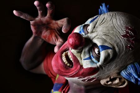 Evil clown: closeup of a scary evil clown against a black background