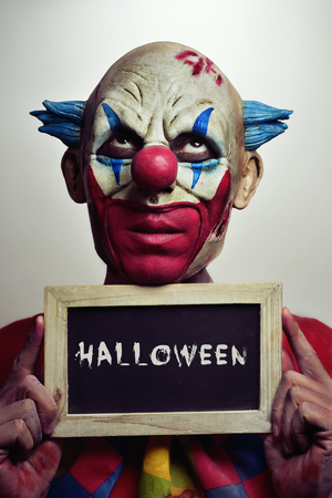 psychopath: portrait of a scary evil clown with a chalkboard with the word Halloween written in it