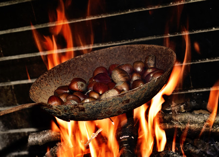 log fire: closeup of a pan with chestnuts being roasted in the flames of a log fire Stock Photo