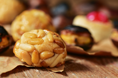 tots: closeup of some roasted chestnuts and some panellets, typical snack in All Saints Day in Catalonia, Spain, and dry leaves on a rustic wooden surface
