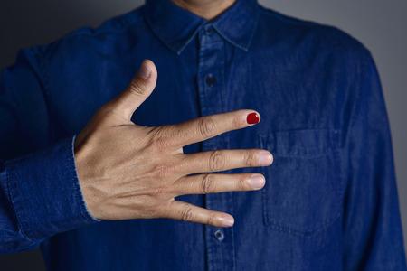 violencia sexual: primer plano de las manos de un hombre joven con una de sus uñas pulido en rojo, en apoyo de los niños víctimas de la violencia física o sexual