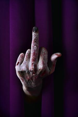 foda: Primer plano de la mano de miedo de un hombre muerto viviente que da el dedo a través de una cortina de la etapa púrpura