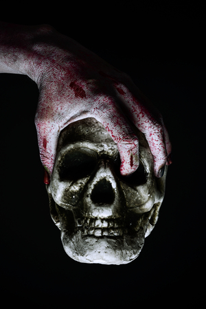living skull: closeup of the scary hand of an undead man holding a skull against a black background