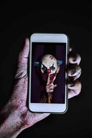 closeup of a scary and bloody hand holding a smartphone with a picture of a scary evil clown asking for silence in its screen Stock Photo