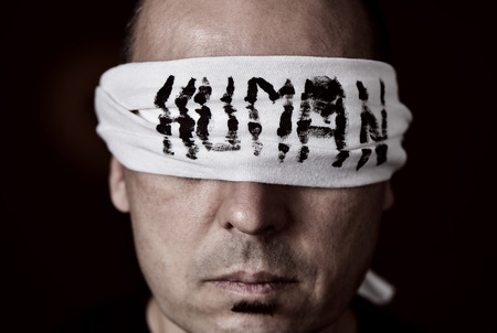 repress: closeup of a young man with a blindfold in his eyes, with the word human handwritten in it Stock Photo