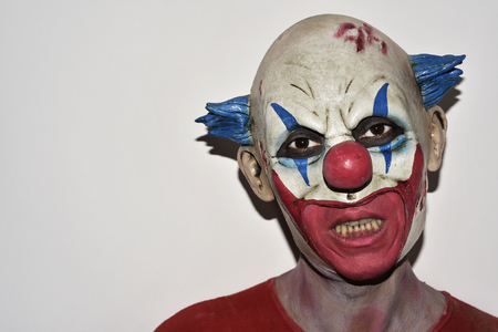 scary halloween: closeup of a scary evil clown against an off-white background Stock Photo