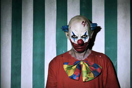closeup of a scary evil clown wearing a dirty costume, with the circus tent in the background Standard-Bild