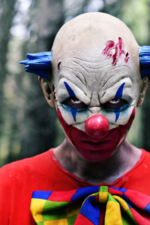 Evil clown: closeup of a scary evil clown staring at the observer, in the woods Stock Photo