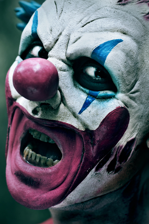 closeup of a scary evil clown with his mouth open showing his rotten teeth staring at the observer