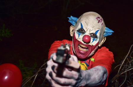 a scary evil clown pointing a gun to the observer in the woods, in the dark of night