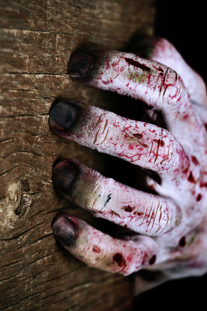 closeup of a scary and bloody hand scratching a rustic wooden surface with his rotten fingernails Stock Photo