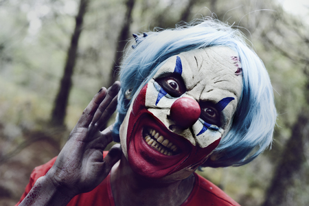 terrifying: closeup of a scary evil clown in the woods touching his blue hair and smiling Stock Photo