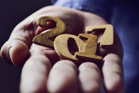 0 1 years: closeup of wooden numbers forming the number 2017, as the new year, in the hand of a young caucasian man Stock Photo