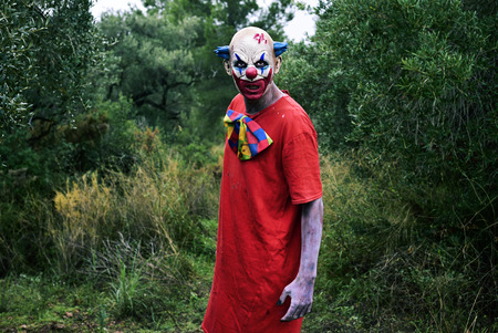 a scary evil clown, wearing a dirty costume, in the woods