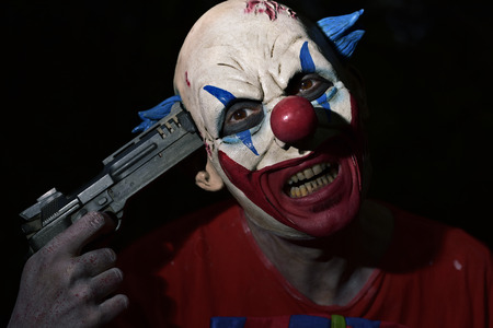 Evil clown: closeup of a scary evil clown pointing a gun to his own temple in the darkness
