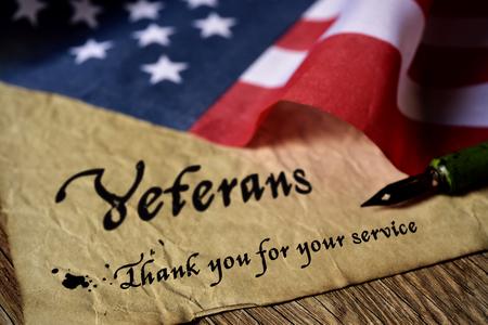 de tekst veteranen dan u voor uw service geschreven in een stuk papier met een penpunt pen en een vlag van de Verenigde Staten, op een rustieke houten achtergrond