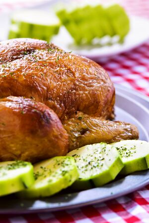 roast turkey: closeup of an appetizing roast turkey in a tray with vegetables, on a table set with a red and white checkered tablecloth Stock Photo