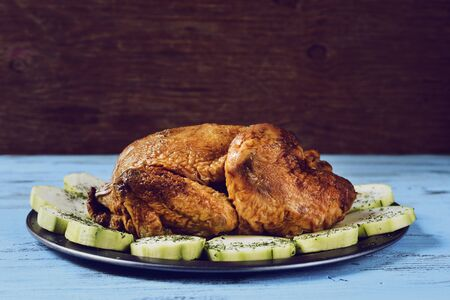 roast turkey: an appetizing roast turkey in a tray with vegetables, on a blue rustic wooden table
